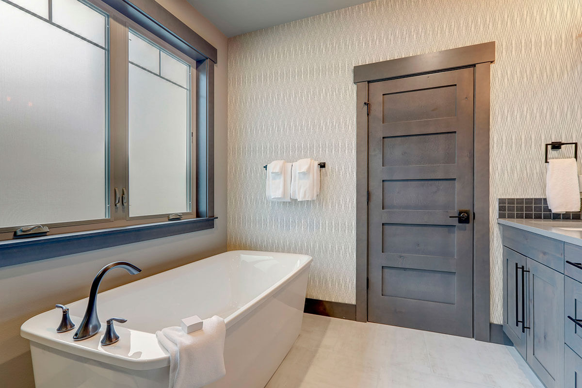 A bathtub next to a large window and on the wall the Gray Weave Peel and Stick