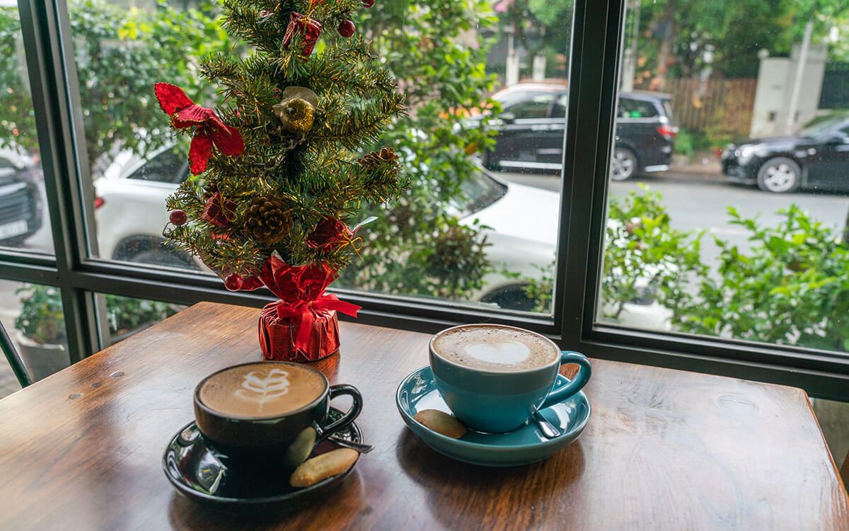 Two lattes on a table with a mini christmas tree