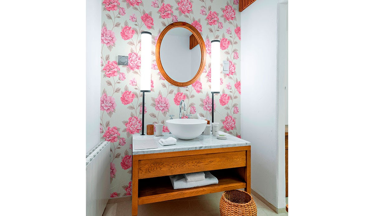 Pink floral wallpaper behind a sink and mirror.