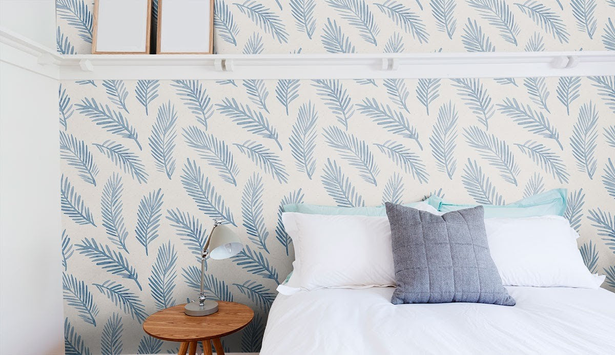 A blue botanical themed wall in a bedroom