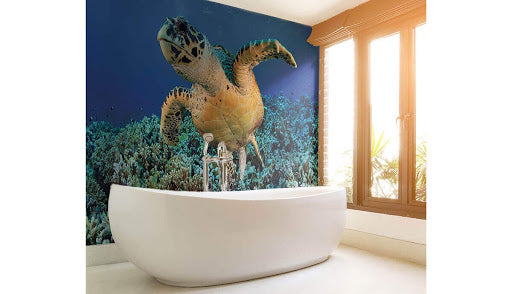 Bathtub in front of a blue turtle wall mural.