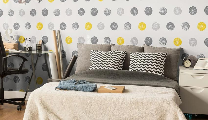 A bedroom with gray and yellow circles on the wall.