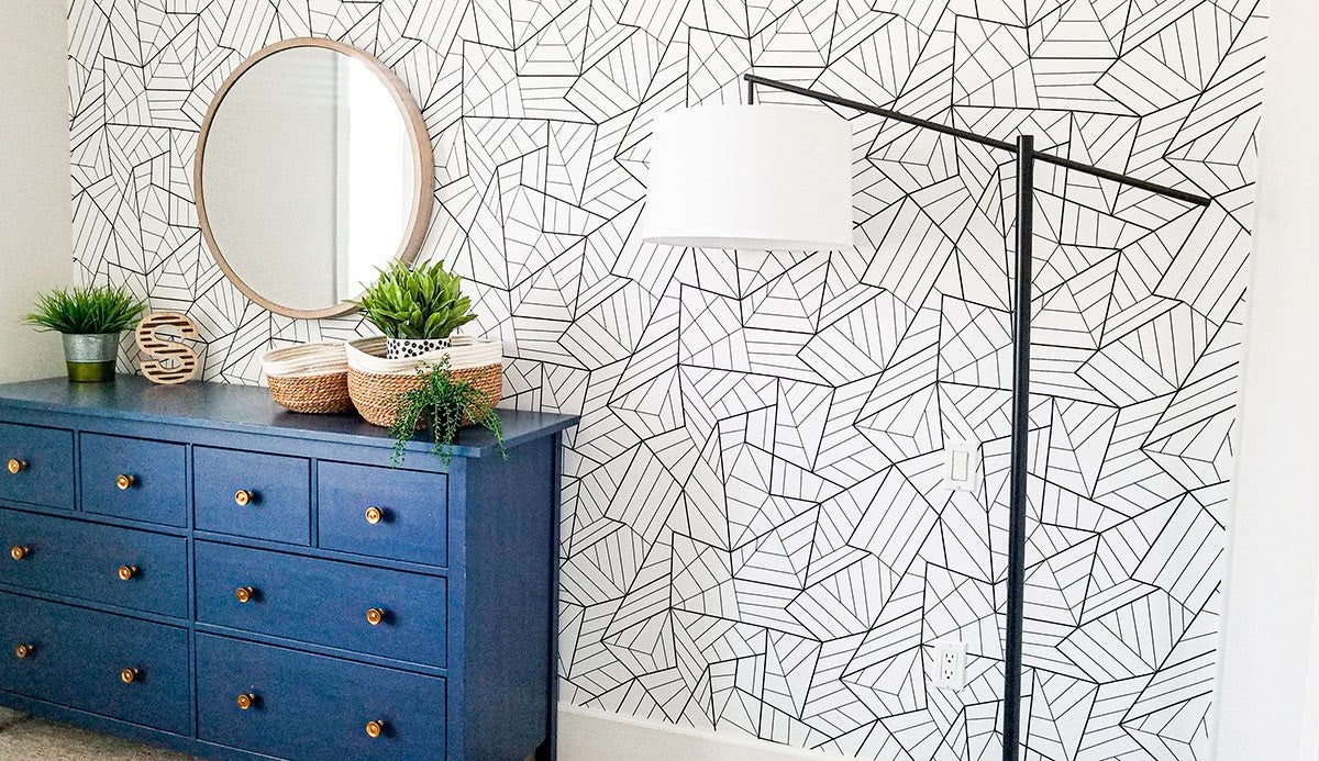 A blue dresser against a wall featuring a black and white geometric design