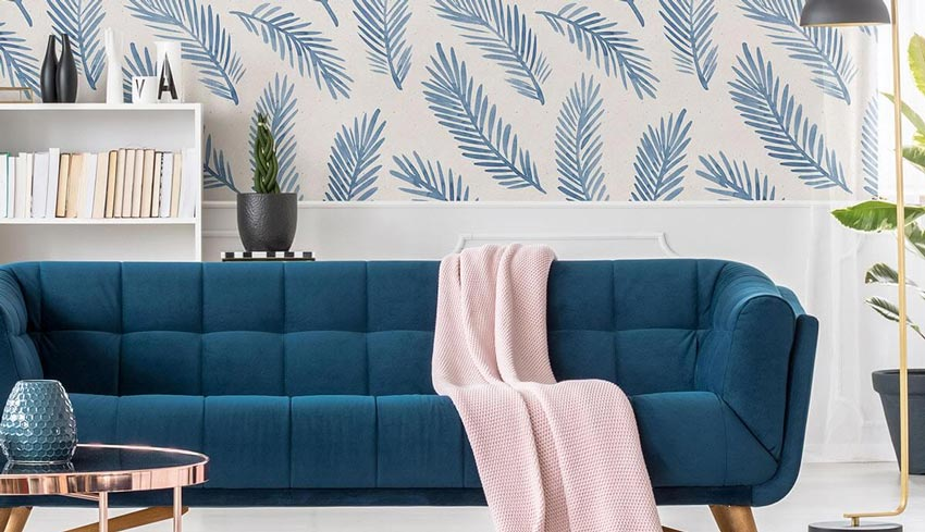 Light blue botanical wallpaper and a long blue couch.
