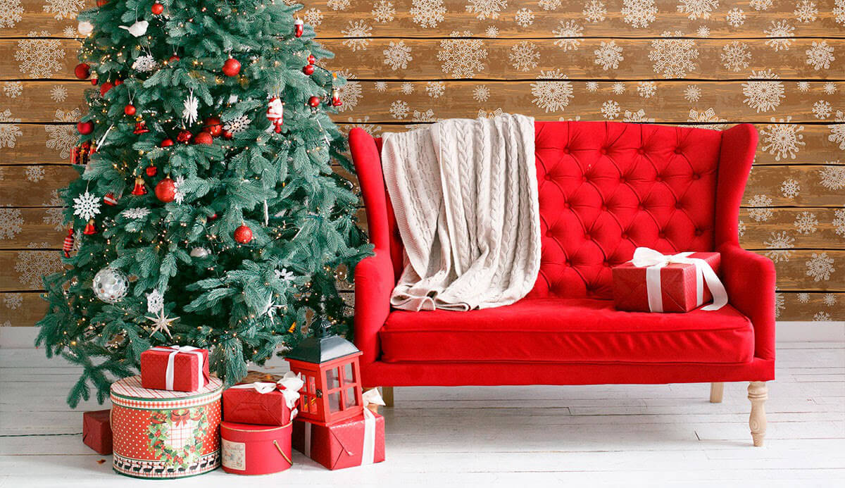 A bright red couch next to a christmas tree with gifts, faux snow wallpaper in the background.