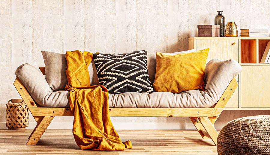 Wood-framed couch in a neutral living room with mustard accents.