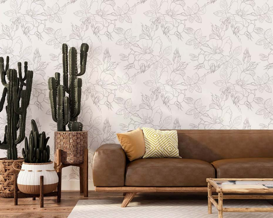 Floral removable wallpaper, a brown couch, and large indoor cacti.