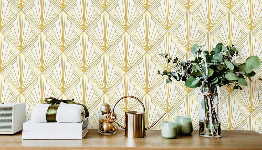 Gold geometric wallpaper and knick knacks on a wooden countertop.