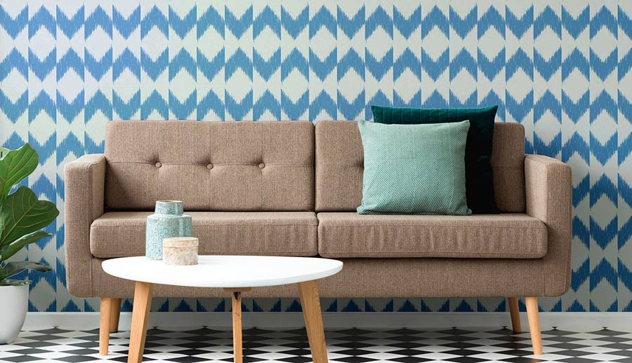 Greige couch with geometric wall treatments and flooring.