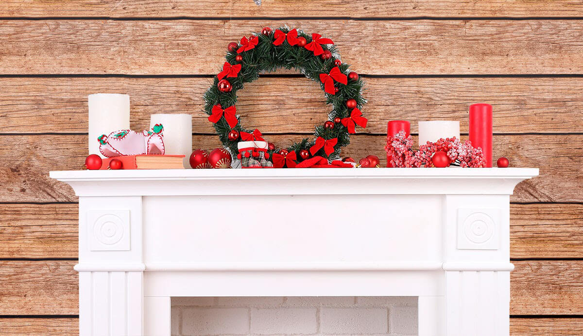 Holiday decor atop a white mantel, with shiplap wallpaper
