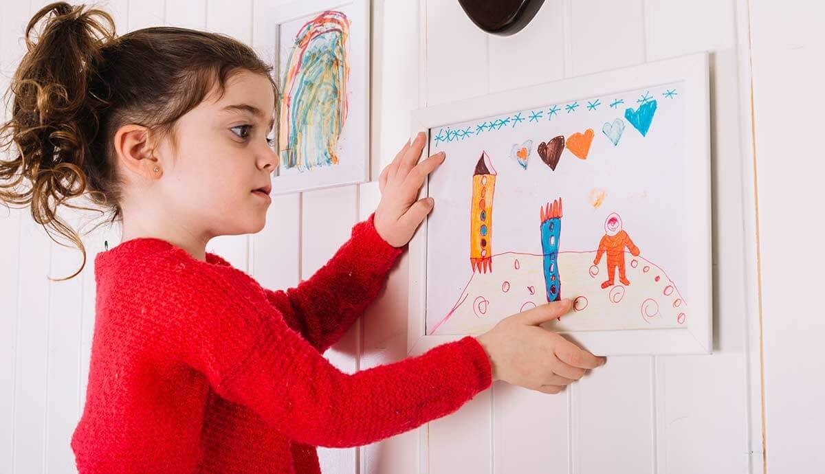 Kid decorating a gallery wall with a hand-drawn picture.