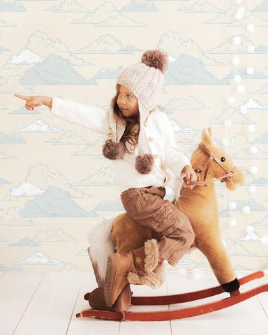 girl pointing while sitting in a rocking horse toy