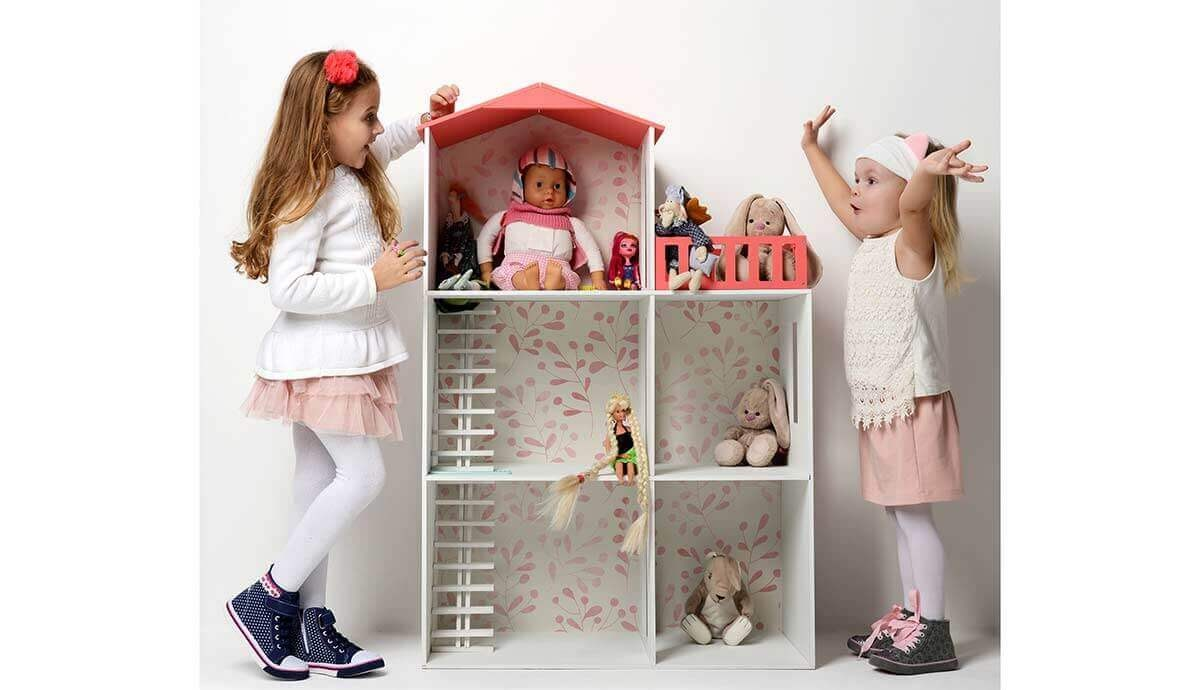 Kids decorating and playing with a dollhouse.