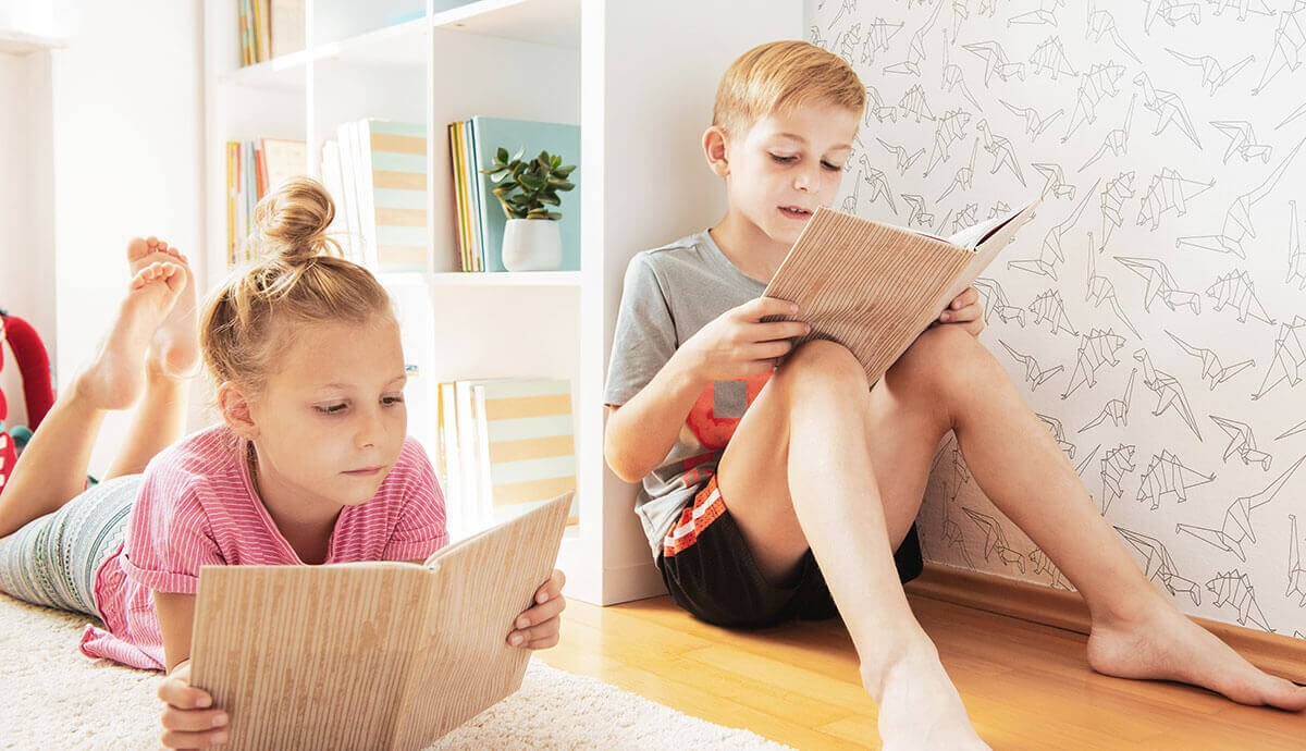Two kids reading next to black animals wallpaper and kid-friendly decor.