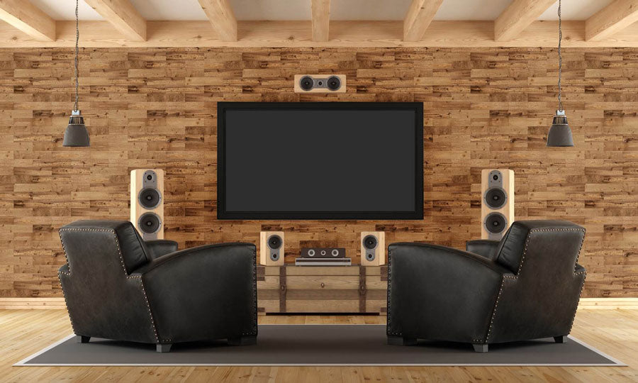 Large wall mounted TV with two leather chairs, faux-wood wallpaper on the walls.