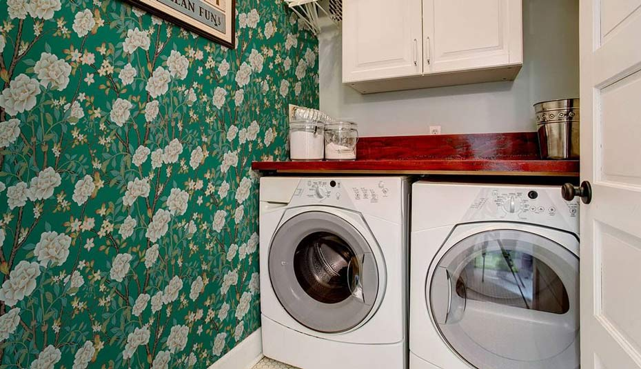 A laundry room decorated with green chinoiserie removable wallpaper.