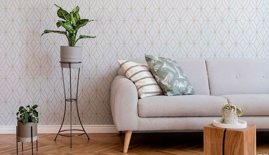 Light and gold geometric wallpaper in a room with light furnishings.