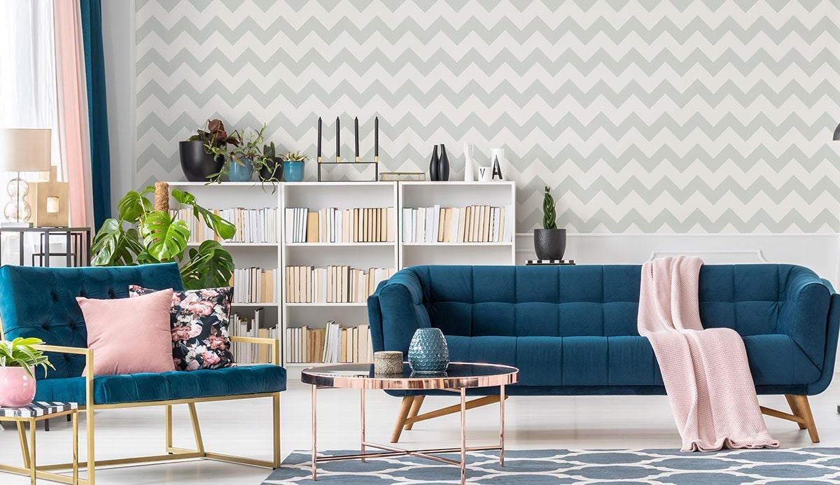 Blue seating and pastel throws in a room with light geometric walls