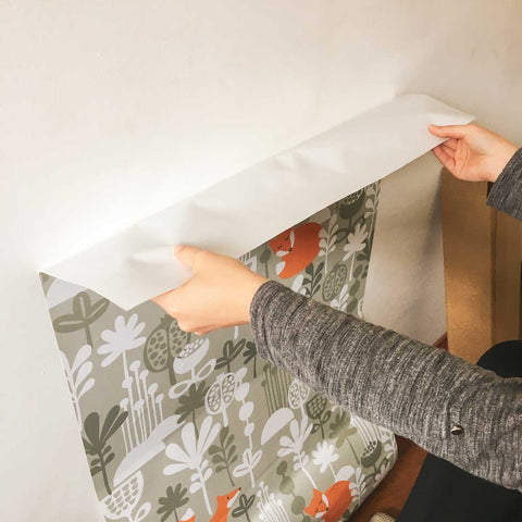 woman applying peel and stick wallpaper on wall