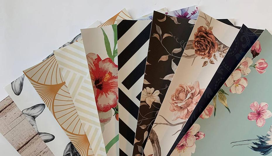 Fanned out samples of fabric peel and stick wallpaper.