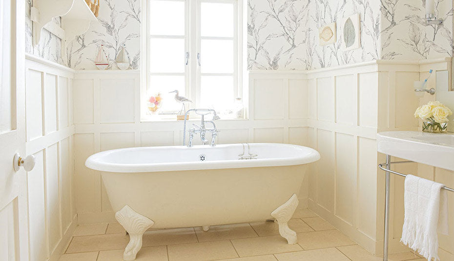 A cleanly decorated bathroom with sketch-like wallpaper.