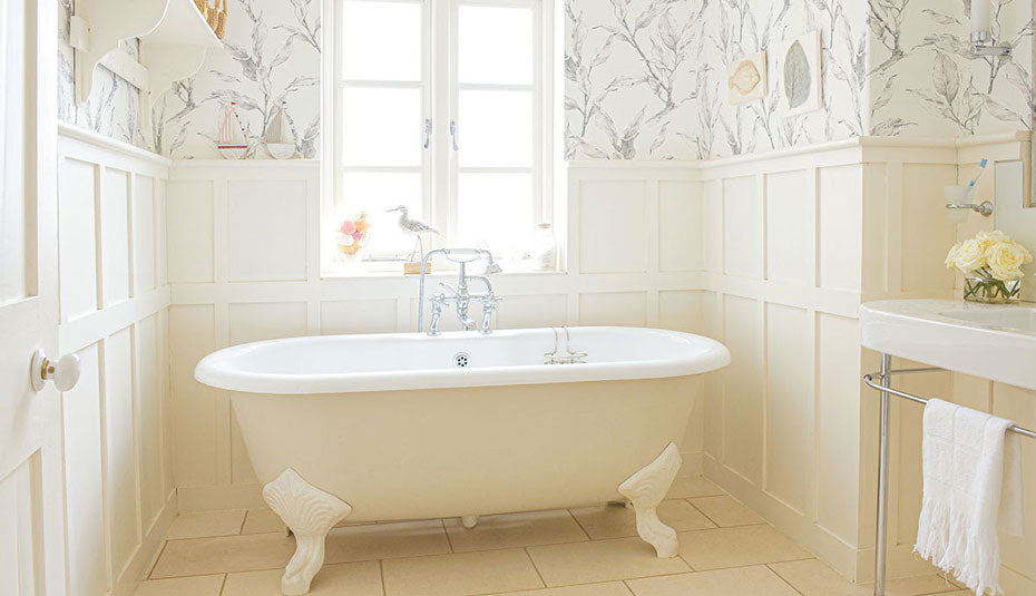 A large bathtub in a room decorated in shades of white.