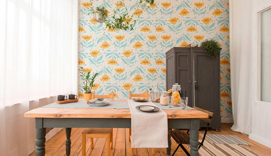 A wooden breakfast table with cheerful floral wallpaper behind it.