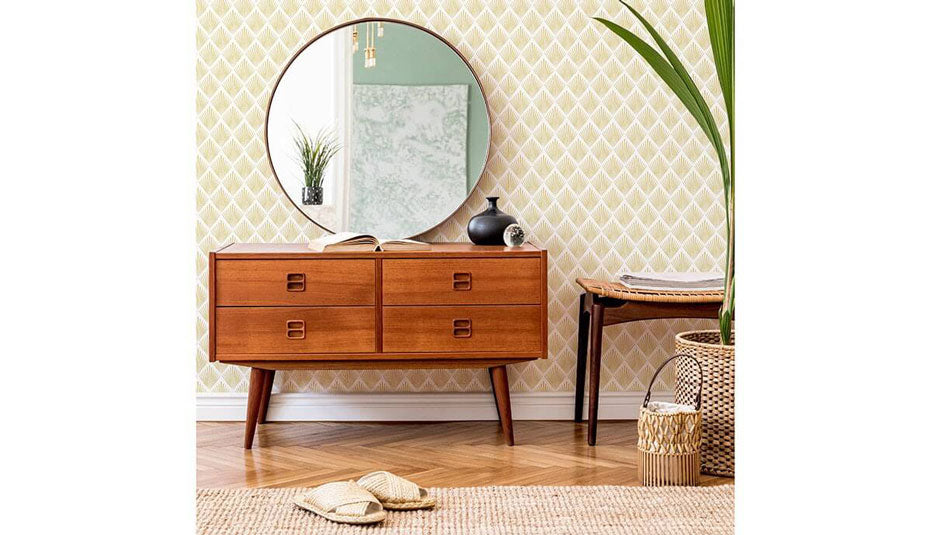 A wooden dresser and vanity mirror in front of a patterned beige wall.