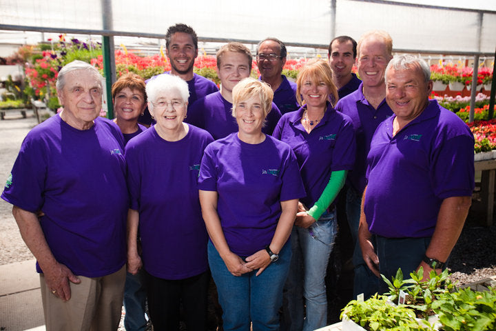 Group of smiling employees standing in front of flower hanging baskets