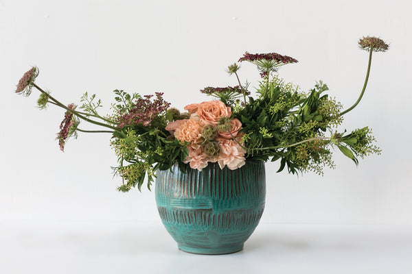 A beautiful textured blue and brown terracotta pot styled with green and peach florals.