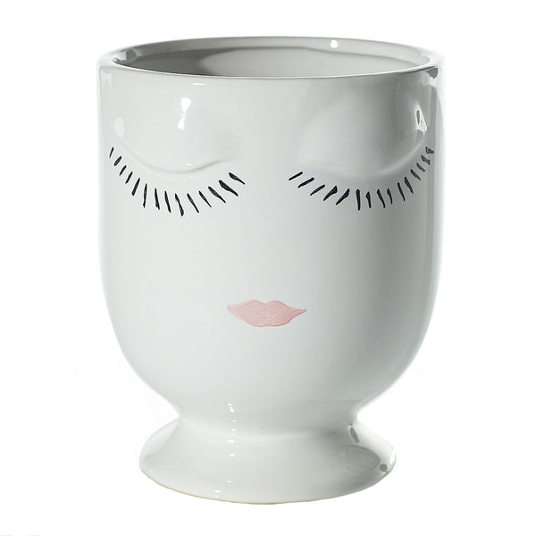 Mini ceramic planters in a shiny, glazed finish with facial accents sculpted and painted on the front in colour white.