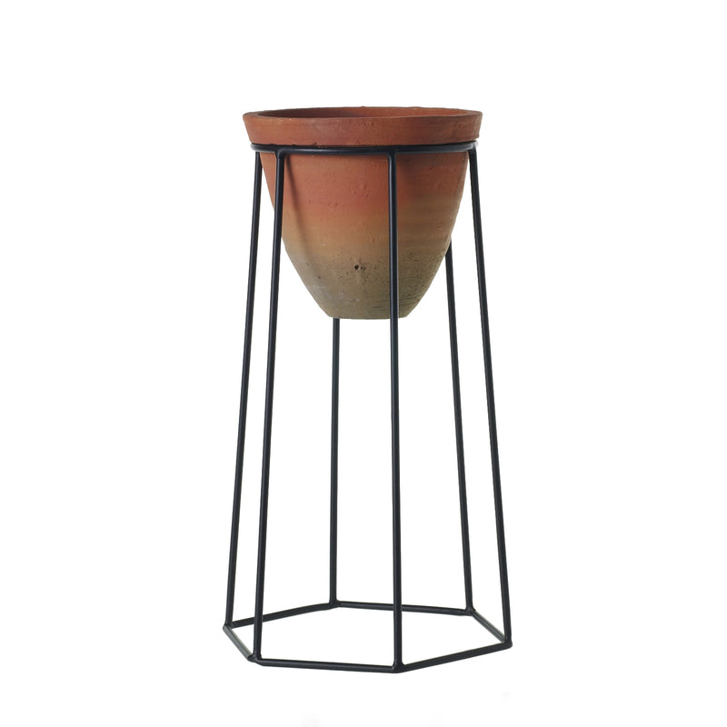 A plant stand with black metal geometric legs and a terracotta pot in size medium.