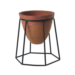 A plant stand with black metal geometric legs and a terracotta pot in size small.