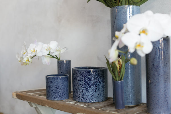 A grouping of different sized pots and vases. The Azura Pot has a glossy finish with white glaze overlay which is hand applied to blue ceramic. Styled with beautiful white orchids.
