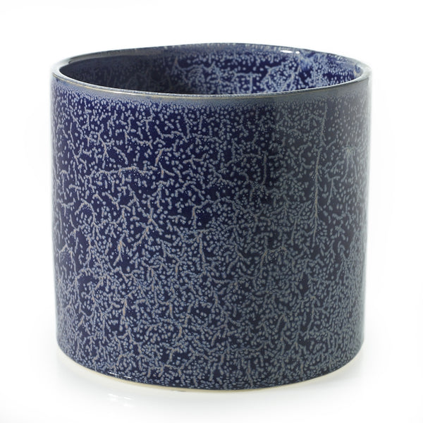 A glossy finish pot with white glaze overlay which is hand applied to blue ceramic.
