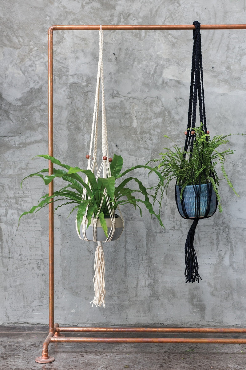 Two woven hangers crafted from jute and enhanced with fringe accents styled with leafy plants.