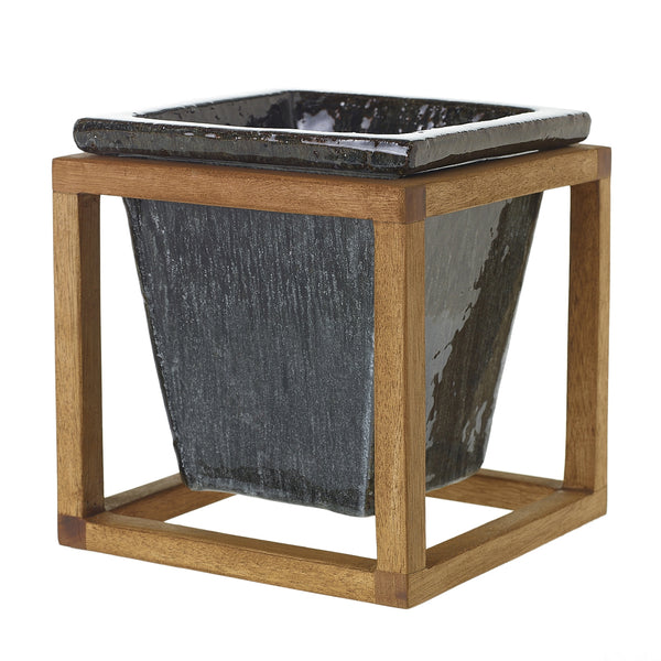 Plant Stand is made of a graphite black stoneware container sitting within a wooden oak frame in size small.