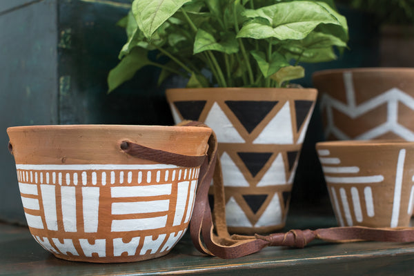 Hanging pot made from terracotta with white accents and adjustable leather straps for hanging next to more tribal painted terracotta pot style with a green plant.