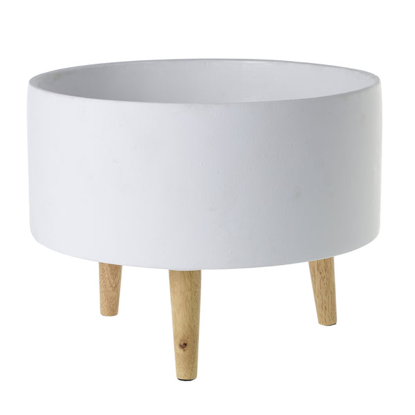 Stoneware cylindrical, standing planter has a matte white container which sits on a trio of tapered wooden dowel legs in size medium.