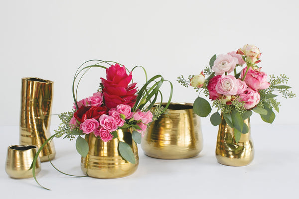 Matte gold ceramic pots in varying sizes with uneven edges and unique eye-catching shapes styled with pink florals.