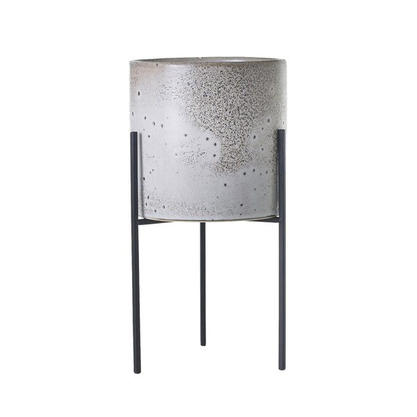 A plant stand featured a grey distressed ceramic pot which sits inside a black rod iron stand with 3 narrow legs in size medium.