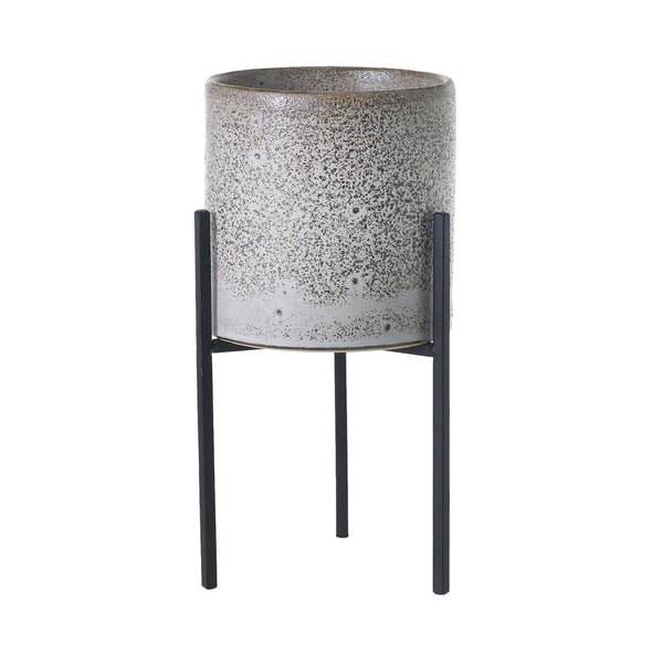 A plant stand featured a grey distressed ceramic pot which sits inside a black rod iron stand with 3 narrow legs in size small.