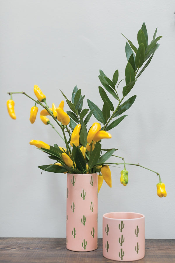 Grouping of two pots. One tall vase and one short container with cactus motif coloured in peach. Styled with green leafy plant and decorative yellow peppers.
