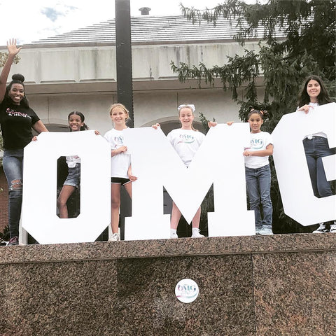 Girls posing with large OMG letters