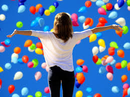 Girl facing hundreds of floating balloons, arms spread with joy