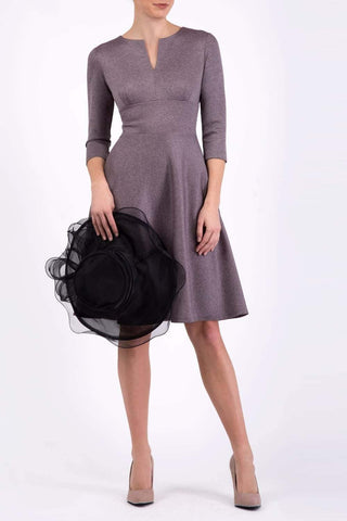 lady in grey dress holding a hat