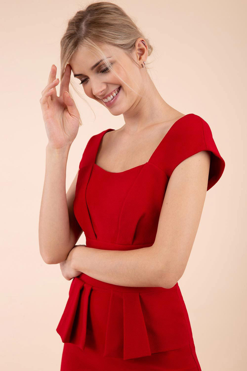A blonde hair Model smiling is wearing red peplum short sleeve dress from Diva Catwalk