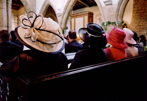 three women wearing hats sitting in a church