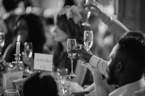 black and white photo of people toasting with glasses
