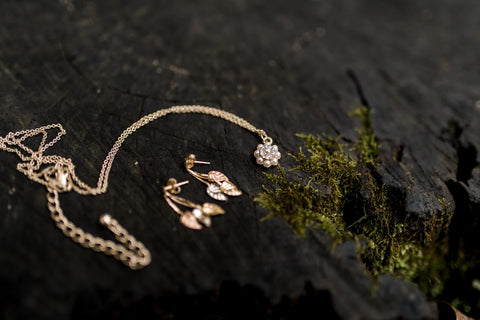 photograph of gold jewellery on a dark wood background